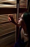 Ängstlich sitzendes dem Gitter durch betrachten der jungen Frau stockfoto