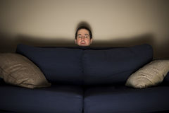 Erschrockener Mann späht über eine Couch beim Fernsehen Stockfotografie