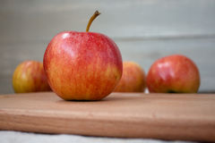 Äpfel auf dem hölzernen Brett Stockfoto