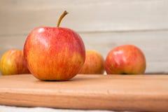 Äpfel auf dem hölzernen Brett Lizenzfreie Stockfotografie