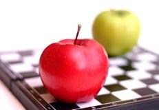 Äpfel auf einem Schachbrett Lizenzfreie Stockbilder
