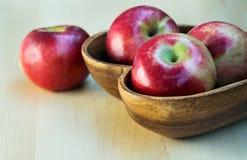 Äpfel in der hölzernen Herzform überziehen auf dem Tisch, nah oben Stockbild