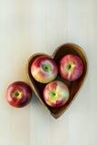 Äpfel in der hölzernen Herzform überziehen auf dem Tisch, nah oben Lizenzfreie Stockfotografie
