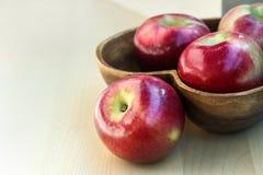 Äpfel in der hölzernen Herzform überziehen auf dem Tisch, nah oben Stockbilder