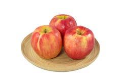 Äpfel in der hölzernen Platte auf einem weißen Hintergrund Lizenzfreie Stockfotos