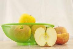 Äpfel in einem Korb auf einem Holzfuß Stockfoto