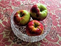 Äpfel in einem Teller mit Blumentischdecke-Hintergrund stockfotografie