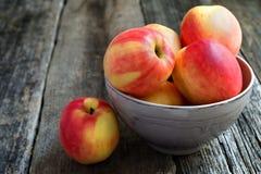Äpfel in einer Schüssel auf einem hölzernen Hintergrund Stockfotos