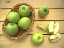 Äpfel grünen reifes und süßes in einem Korb und schneiden in Stücke Lizenzfreies Stockfoto