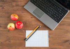 Äpfel, Laptop, Notizbuch und Bleistifte Stockbild