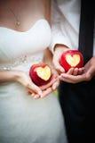 Äpfel mit einem Herzen in den Händen Lizenzfreie Stockfotografie