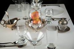 Äpfel mit Gläsern und Tischbesteck Stockbilder
