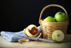 Äpfel mit Messer und Korb Stockfotografie