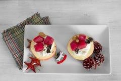 Äpfel mit Sahne angefüllt und Frucht auf weißer Platte Stockfotos