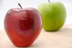 Äpfel rot und grün auf hölzerner Tabelle Lizenzfreie Stockfotografie