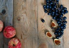 Äpfel, Trauben und Feigen auf hölzernem Hintergrund Lizenzfreie Stockbilder