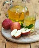 Äpfel und Apfelsaft auf einem hölzernen Behälter Lizenzfreie Stockfotografie