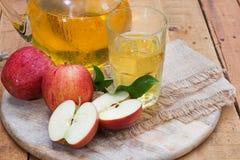 Äpfel und Apfelsaft auf einem hölzernen Behälter Stockfotografie