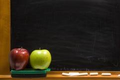 Äpfel und Challkboard an der Schule Stockfotos