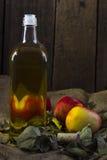 Äpfel und eine Flasche Öl Stockfotos