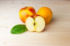 Äpfel und eine Orange auf einem hellen Hintergrund Lizenzfreie Stockfotos