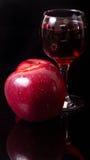 Äpfel und Glas Wein auf einem schwarzen Hintergrund Lizenzfreies Stockfoto