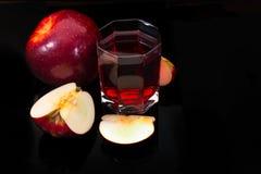 Äpfel und Glas Wein auf einem schwarzen Hintergrund Stockfotografie