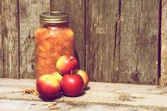 Äpfel und Konserven auf Holz. Lizenzfreie Stockbilder