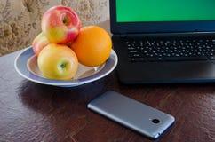 Äpfel und Orangen auf einer Platte nahe bei einem Laptop, intelligentes Telefon auf dem Tisch Stockbild