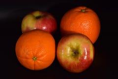 Äpfel und Orangen auf Schwarzem Stockbild