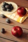 Äpfel und Pflaumen auf einem Holztisch Stockbild