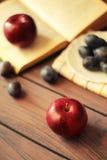 Äpfel und Pflaumen auf einem Holztisch Lizenzfreie Stockfotografie