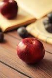 Äpfel und Pflaumen auf einem Holztisch Stockfotos