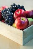 Äpfel und Trauben in einer Holzkiste, Abschluss oben, selektiver Fokus Lizenzfreies Stockfoto