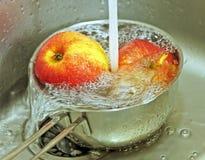 Äpfel und Wasser spritzt in einer Stahlwanne Lizenzfreies Stockbild