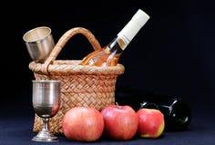 Äpfel, Weinglas und Flasche im Korb Stockfoto