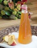 Äppelcider och nya äpplen på träbakgrund Arkivfoto