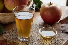 Äppelcidervinäger i ett exponeringsglas, med äpplen i bakgrunden royaltyfria foton