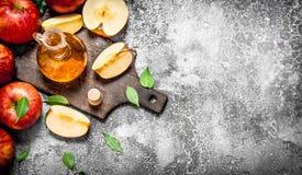 Äppelcidervinäger med nya äpplen på skärbräda royaltyfri bild