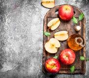 Äppelcidervinäger med nya äpplen på skärbräda arkivfoto
