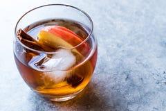 Äppelciderwhiskycoctail med kanelbruna pinnar, is och Apple skivor royaltyfria bilder