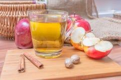 Äppeljuice - varma äppledrink och äpplen för alkohol på trätabellen Fotografering för Bildbyråer
