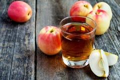 Äppelmust i ett exponeringsglas och äpplen på träbakgrund Arkivfoto