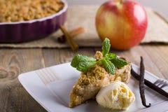 Äppelpaj med glass som dekoreras med vanilj, mintkaramellen och kanel på träbakgrund Ett läckert stycke av kakan med is Arkivbilder