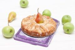Äppelpaj med päronet på purpurfärgad skärbräda Royaltyfri Bild