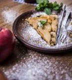 Äppelpaj på en träbakgrund med äpplen Arkivfoto