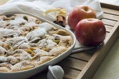 Äppelpaj på en vit platta och två äpplen, wood bakgrund Arkivfoto