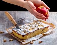 Äppelpaj som dammas av med det pudrade socker och snittet med en kniv Hand Arkivfoto