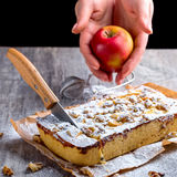 Äppelpaj som dammas av med det pudrade socker och snittet med en kniv Hand Arkivbild