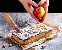 Äppelpaj som dammas av med det pudrade socker och snittet med en kniv Hand Fotografering för Bildbyråer